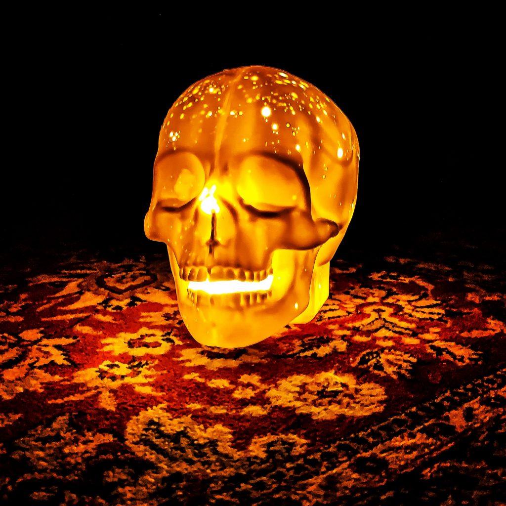 Lampe en porcelaine en forme de crâne humain, posée sur un tapis ancien. Pièce unique lumineuse.